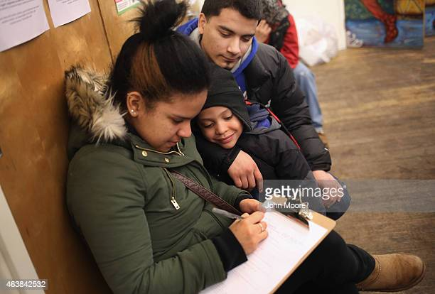 A family fills out an application for Deferred Action for Childhood Arrivals at a workshop on February 18 2015 in New York City The immigrant...
