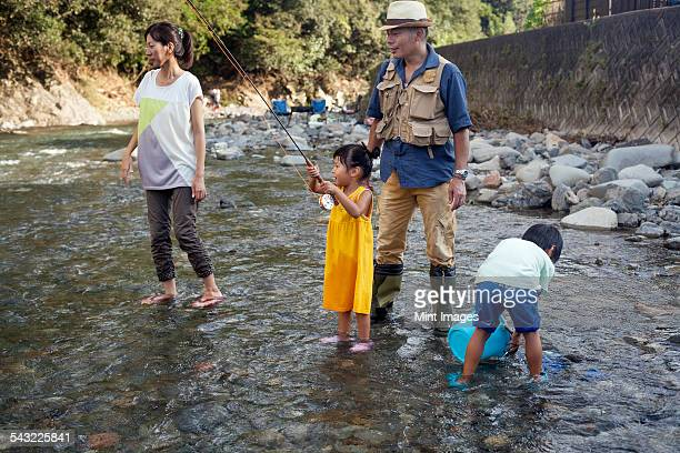 Family fishing in a stream.