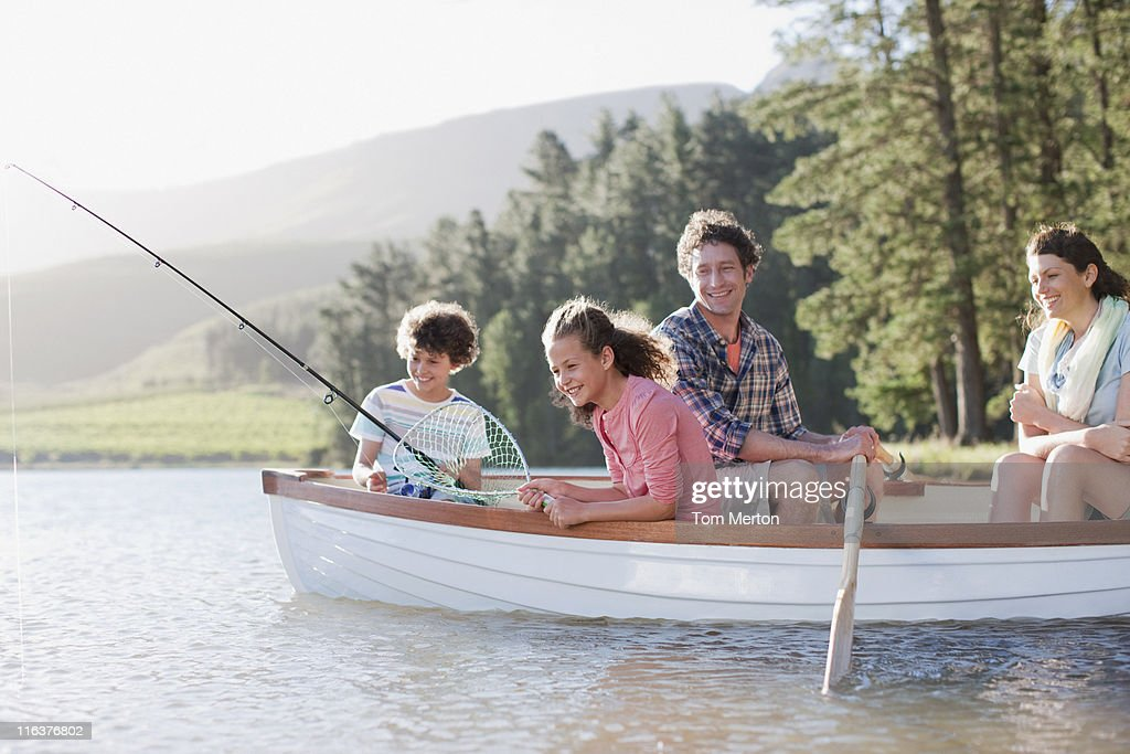 Family fishing in boat on lake : Stock Photo