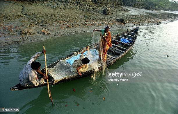 A family fishing on the river in the Sundarbans The worlds largest littoral mangrove forest by the Bay of Bengal the Sundarbans has been declared a...