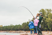 side view of young family fishing together