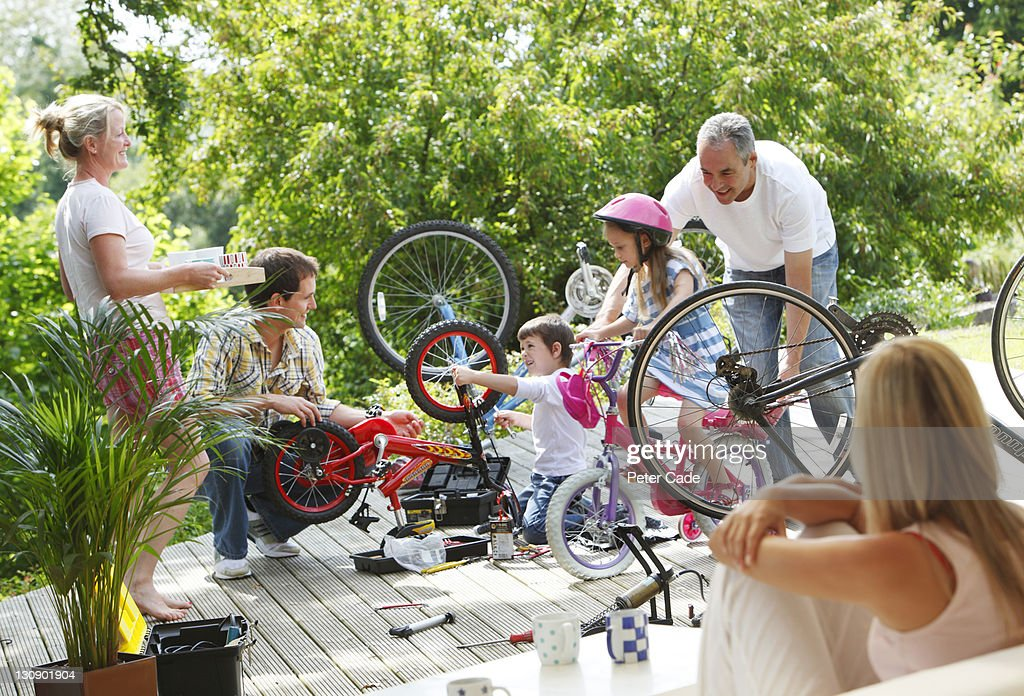 family fixing bike outside : Stock Photo