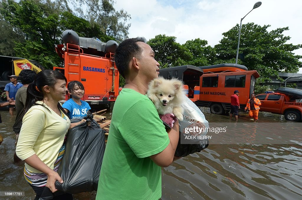 A family flees from home with their dog Chloe as floodwater submerged part of North Jakarta, in Jakarta on January 21, 2013. Companies and consumers have started to calculate damages and losses from the widespread floods that hit Jakarta last week, claiming at least 15 lives, displacing thousands from their homes and afflicting capital residents with water-borne illnesses, a local newspaper reported.