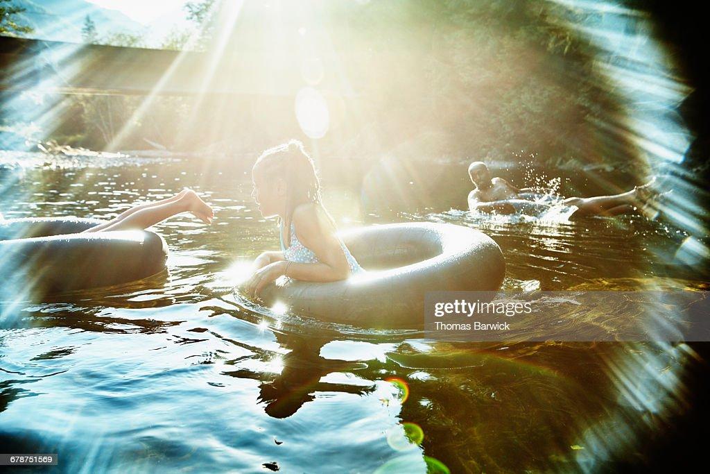 Family floating on inner tubes on river : Stock Photo