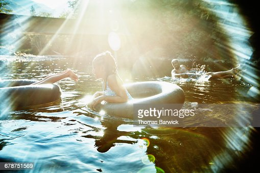 Family floating on inner tubes on river