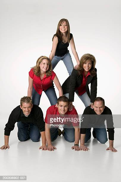 Family forming human pyramid in studio, portrait