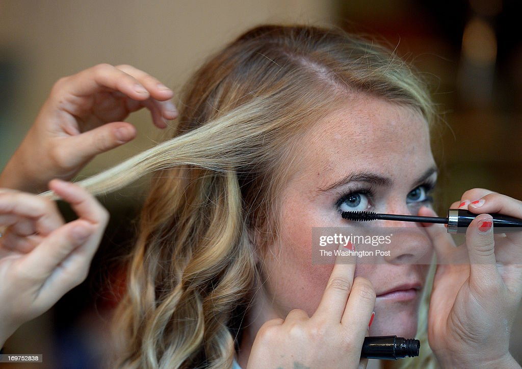 Family friend Arianna Ackman, left, works on her hair while Westfield High School senior and girls' varsity soccer captain Carolyn Seltzer, center, has her sister Molly Seltzer do her make up while quickly getting ready for prom after playing in the Concorde District Final against Chantilly at Westfield High School on Friday, May 17, 2013.