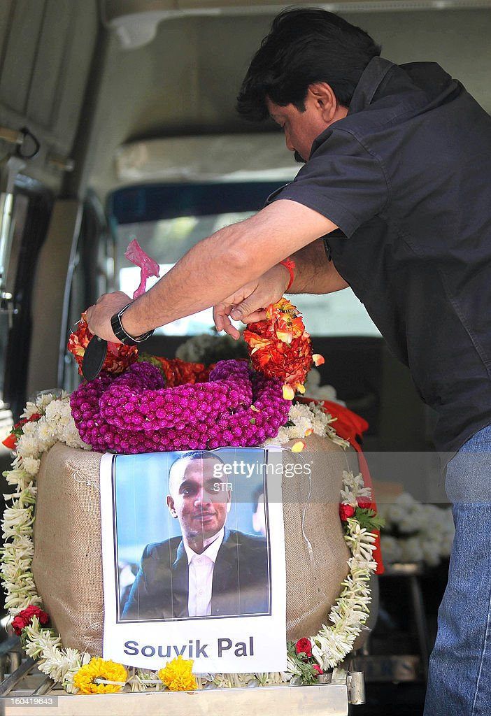 A family friend lays a wreath on the coffin containing the body of 19-year-old Souvik Pal inside the hearse outside the family residence in Bangalore on January 31, 2013. Souvik Pal, a student of Manchester Metropolitan University, was found dead in a canal at Old Trafford in Manchester on January 22, about three weeks after he mysteriously went missing from a night club on New Year's eve.
