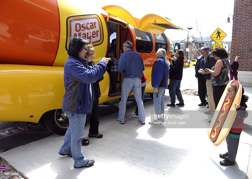 Family friend Sandy Mui, left, and Rochelle Cavagnaro, second from left, take a photo of Cavagnaro's grandson, Deovanni Cavagnaro-Webb, 5, as he poses as a hotdog in front of the Wienermobile. The Oscar Mayer Wienermobile rolls through the metro area on its voyage across the country celebrating the 25th anniversary of having the giant hot dog piloted by recent college grads. The grads, who are part of the 'hotdogger tradition', must attend two weeks of 'Hotdog High' in Madison Wisconsin and serve as drivers and ambassadors of all things Oscar Mayer for one year. There is still a chance to see the road dog before it hits the highway on its return to Wisconsin from 11 a.m.- 4 p.m Saturday at the Walmart at 440 Wadsworth Blvd. in Lakewood.