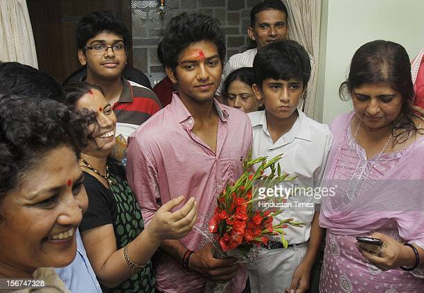 'NEW DELHI INDIA AUGUST 30 Family friends' present flower to India U19 cricket captain Unmukt Chand and his Mother Rajeswar Chand on August 30 2012...