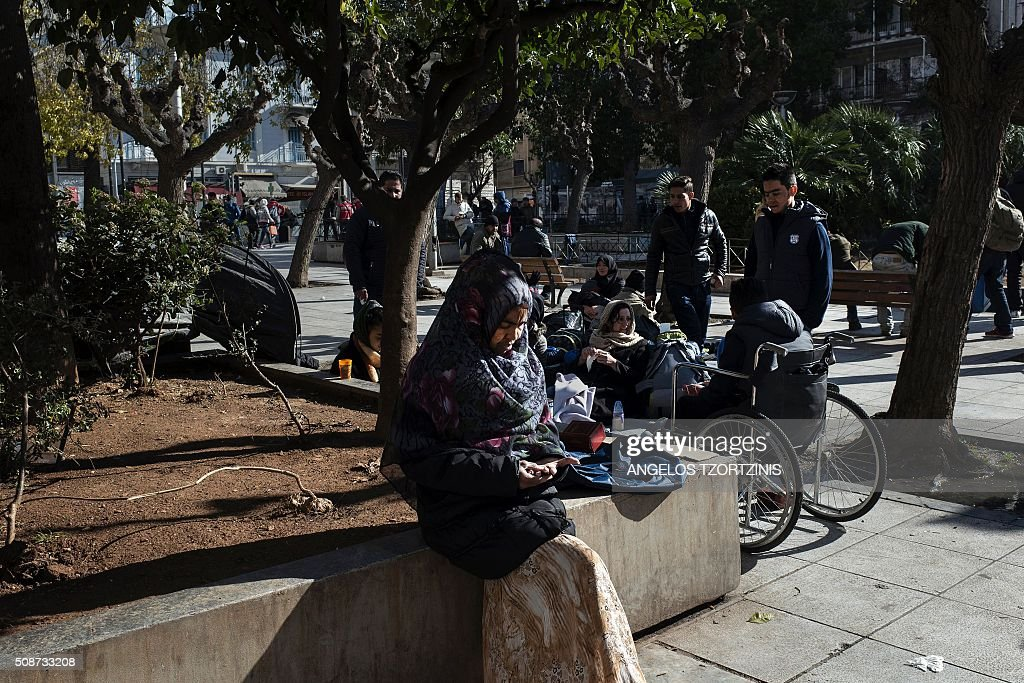A family from Afghanistan sits under trees in Victoria Square, where migrants and refugees found temporary refuge, in central Athens on Frbruary 6, 2016. More than a million migrants landed in the 28-nation European Union last year, most of them crossing into Greece from Turkey, and then making their way through the Balkans to Germany and other northern member states. / AFP / ANGELOS TZORTZINIS