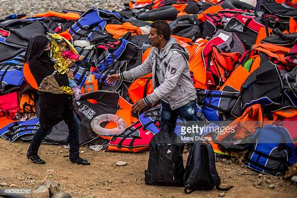 A family from Syrian town Aleppo stands in front of a mound of life jackets as they arrive with other refugees on the shores of the Greek island of...