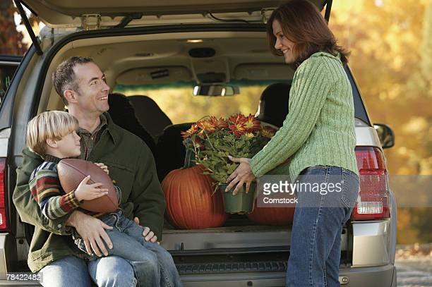 Family gathered around back of SUV loaded with apples and pumpkins