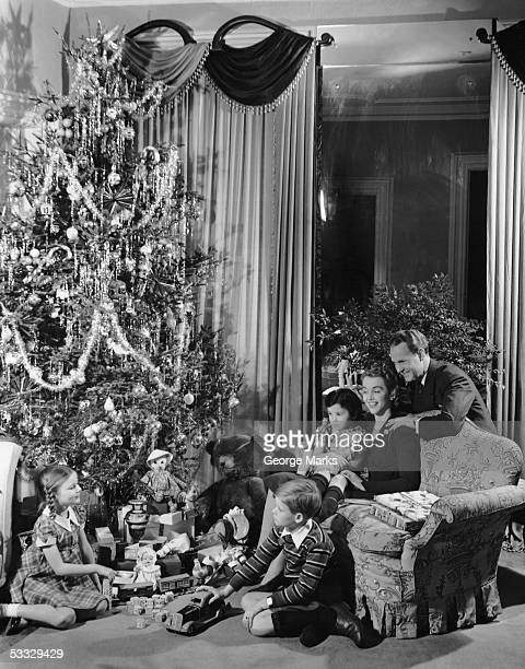 Family gathered around Christmas tree with gifts