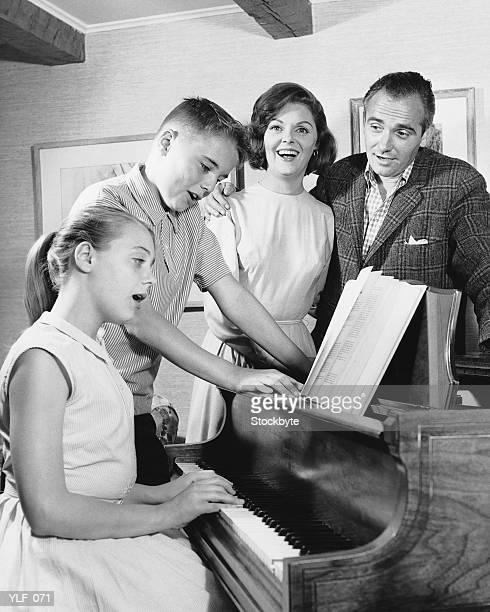 Family gathered around piano, singing