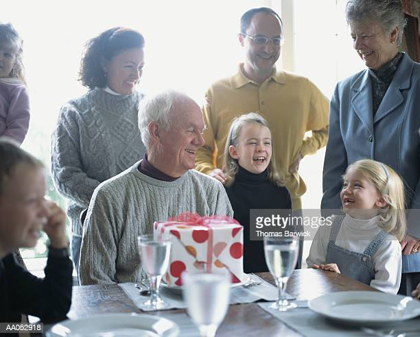 Family gathering around table for grandfather's birthday celebration