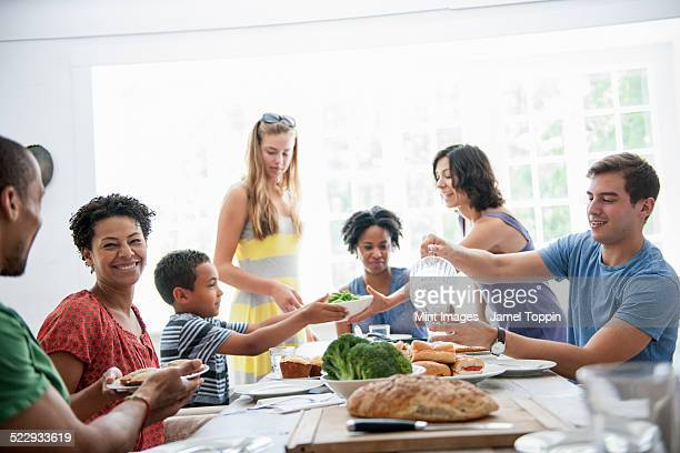A family gathering for a meal. Adults and children around a table.