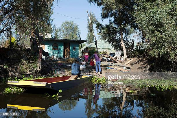 A family gathers on the dock next to their 'trajinera' or gondola on an artificial island or 'chinampa' on a canal at Lake Xochimilco in Mexico City...