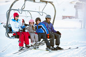 Family Getting Off Chair Lift On Ski Holiday In Mountains Wearing Ski Gear