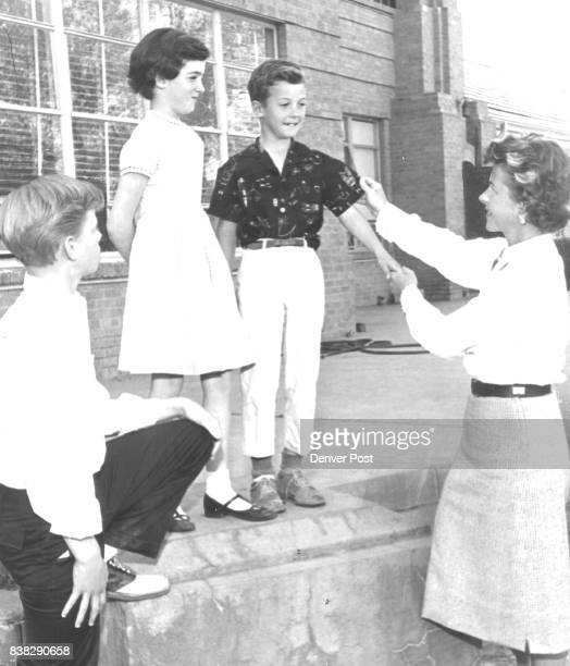 MAY 1 1959 MAY 10 1959 ***** Family GetTogether Mrs Harry Combs sizes up Diane and Jimmy Arneill for the costumes they will wear at the event while...