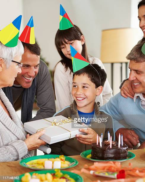 Famille donnant un cadeau à un petit garçon dans son anniversaire