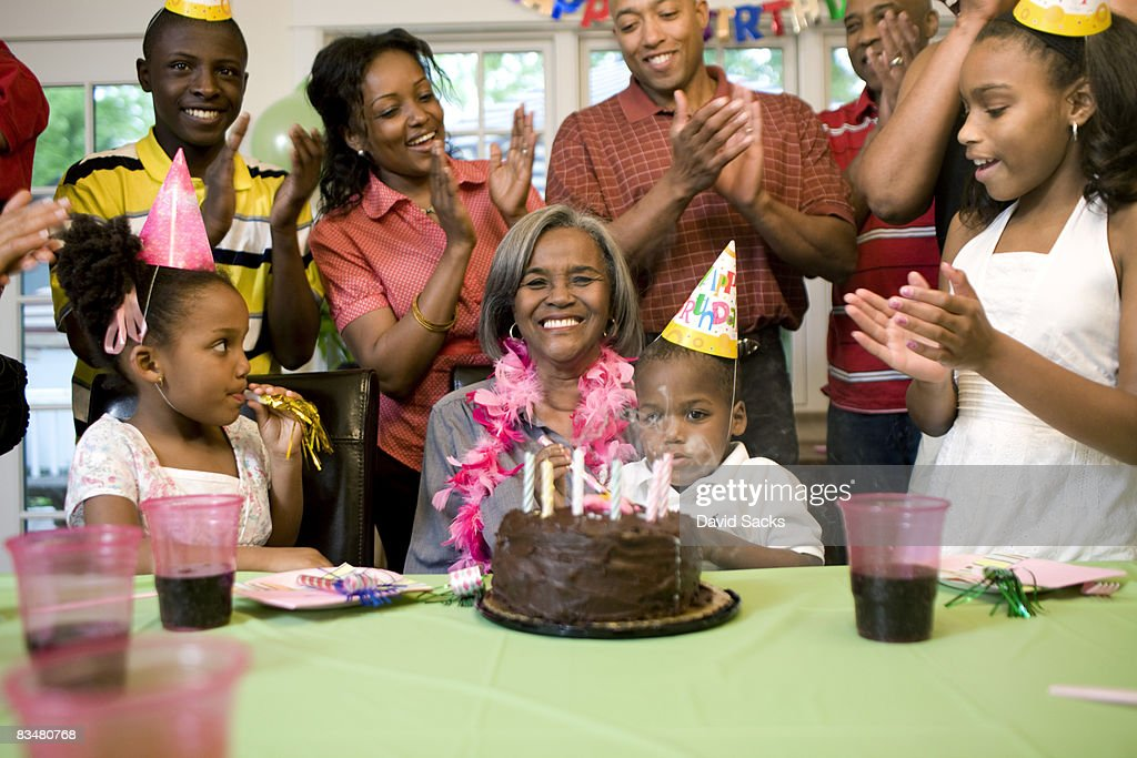 Family giving birthday party to grandmother : Stock Photo