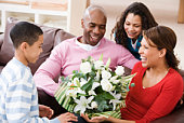 Family giving mother flowers