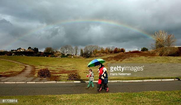 Family goes under an umbrella, on sky rainbow