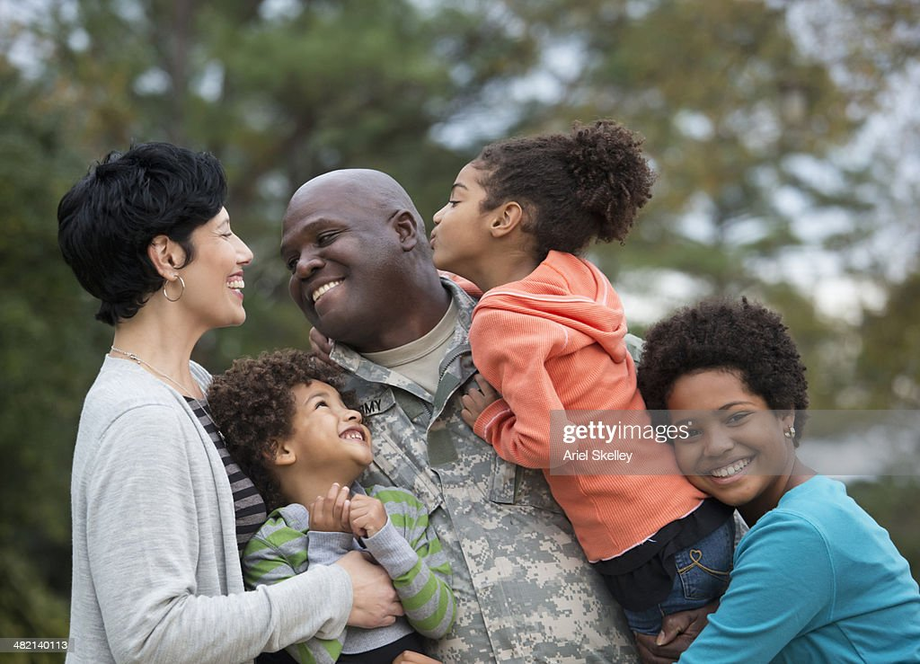 Family greeting returning soldier outdoors