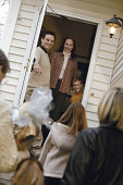 Family greeting visitors in doorway of home