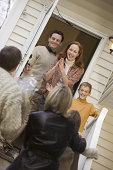 Family greeting visitors on porch