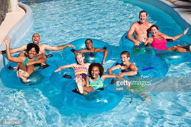 Family groups on inner tubes at water park