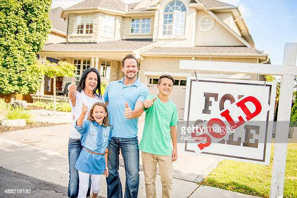 Family Happily Standing Outside of Their Sold Home