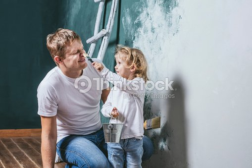 family happy daughter with dad doing home repair paint walls