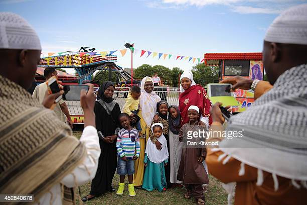 A family has their photograph taken after morning prayers during an Eid celebration in Burgess Park on July 28 2014 in London England The Muslim...