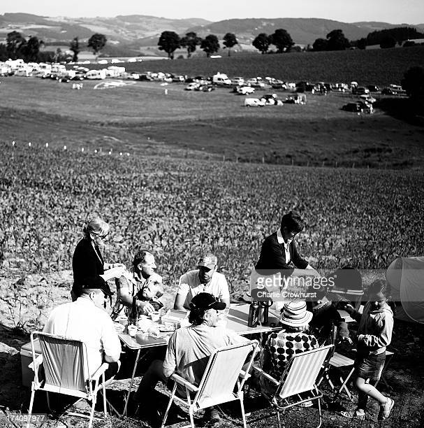 A family have a spot of lunch in a field before the race while campers vans park up by the road in the background during stage fourteen of the 2013...