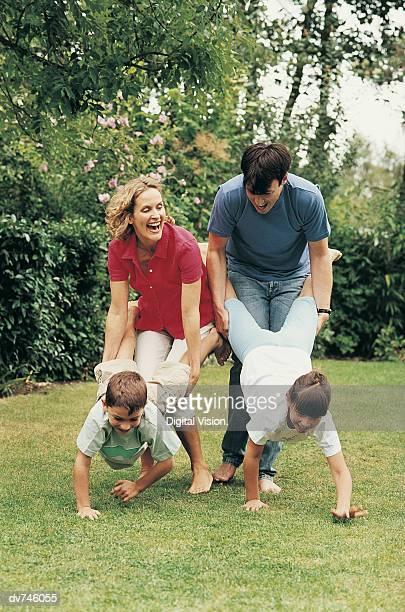 Family Having a Wheelbarrow Race in Their Garden