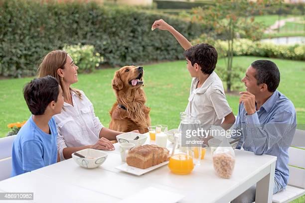 Family having breakfast and feeding the dog