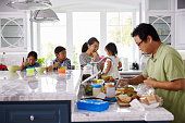 Family Having Breakfast And Making Lunches In Kitchen