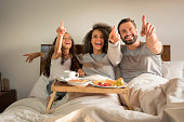Interracial family, lying on the bed, with a surprised face, while they have breakfast on a tray on the bed and point something out