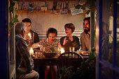 Family having cozy dinner en garden house