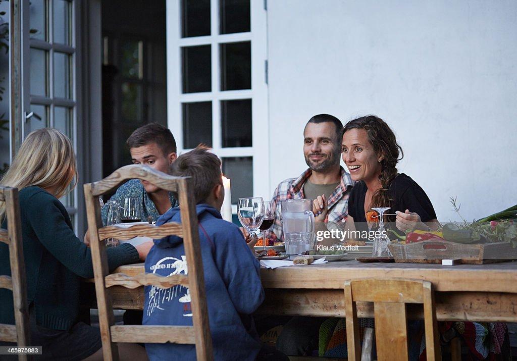 Family having dinner at outside dinner table