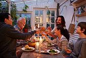 Family having dinner in greenhouse, passing bread