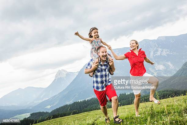 Family having fun and running through meadow, Tyrol, Austria