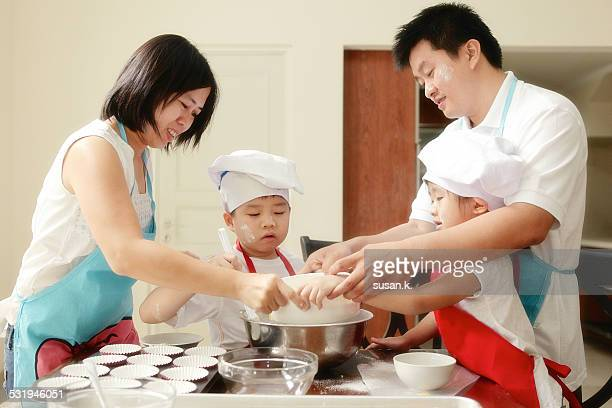 Family having fun baking muffin together