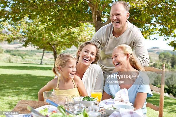 Famiglia divertendosi su tavolo per la prima colazione in giardino