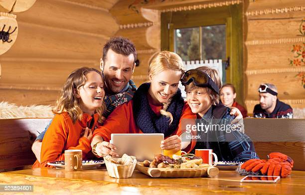 Family having lunch after skiing, using digital tablet