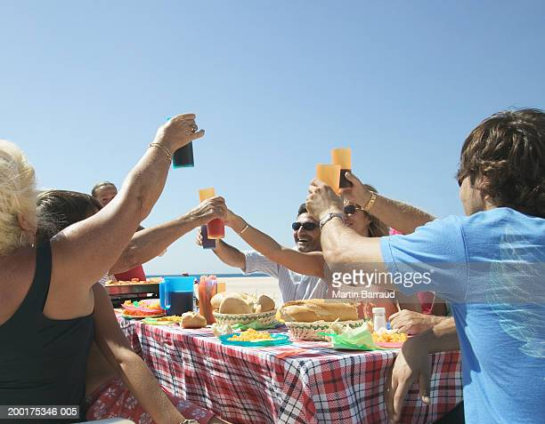 Family having lunch at table on beach, toasting drinks