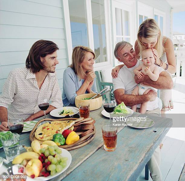 Family having lunch, grandfather holding baby girl (6-9 months)
