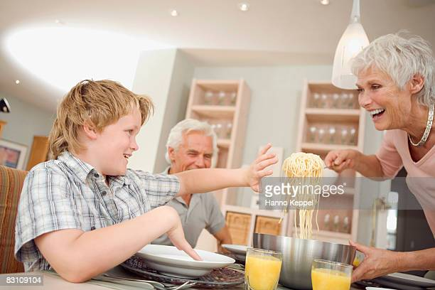 Boy (10-11) with grandparents at dinning table